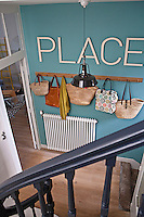 In the entrance hall wicker baskets and shopping bags hang from a Shaker-style clothes rack