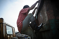 Taupik, 14, climbing down from a truck after searching it for plastic waste at the 'Trash mountain', Makassar, Sulawesi, Indonesia.