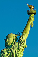 Statue of Liberty holding torch back view blue sky