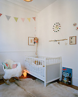 An animal skin rug and rocking chair covered in fake fur soften the white colour scheme of this baby's bedroom