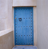 This studded wooden door is painted in a shade of blue used traditionally in Marrakech, Essouira and Assila in Morocco