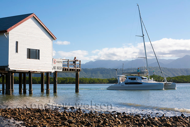 A yacht heads out to sea past the historic Sugar Wharf building.  Port Douglas, Queensland, Australia