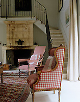 The chairs in this living room are cleverly upholstered in traditional French check fabrics which all have a slightly different pattern