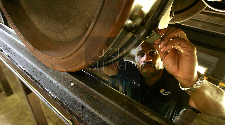 Raymond Clark checks the measurements of a wheel on a rehabilitated rail car at the MARTA Avondale Yard in Decatur, Ga. on Tuesday, July 11, 2006. Joe J. Erves, MARTA'S chief engineer of railcar rehabilitation and reliability, said the rail cars have a useful life of about 30 years, broken down in two 15-year segments with a &quot;mid-life overhaul&quot; in between. The wheels, he added, are good for about 250,000 miles or three years.<br />