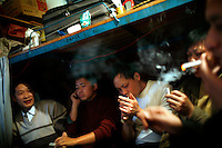 Textile workers smoke in their dormitory at a garment factory. The factory, which specifically carries out a wear-and-tear process used to achieve a fashionable distressed look, produces approximately 10,000 pairs of jeans every day. Thousands of workers labour through the night scrubbing, spraying and tearing jeans in order to meet the production demand. The factory is owned by Huang Dehong, who left his impoverished village and arrived penniless in Zhongshan twenty years ago. China, the &quot;factory of the world&quot;, is now one of the world's largest producers of jeans and its textile workers are among the 200 million migrant labourers criss-crossing the country looking for a better life.
