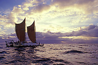Double hulled Poynesian voyaging canoe, the Hokulea, in Kaiwi channel near sunset, island of Oahu off in distance