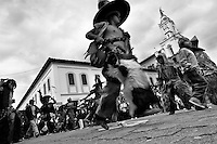 Indians, wearing goatskin chaps, dance furiously during the Inti Raymi (San Juan) festivities in front of the church in Cotacachi, Ecuador, 29 June 2010. 'La toma de la Plaza' (Taking of the square) is an ancient ritual kept by Andean indigenous communities. From the early morning of the feast day, various groups of San Juan dancers from remote mountain villages dance in a slow trot towards the main square of Cotacachi. Reaching the plaza, Indians start to dance around. They pound in synchronized dance rhythm, shout loudly, whistle and wave whips, showing the strength and aggression. Dancers from either the upper communities (El Topo) or the lower communities (La Calera), joined in respective coalitions, seek to conquer and dominate the square and do not let their rivals enter. If not moderated by the police in time, the high tension between groups always ends up in violent clashes.
