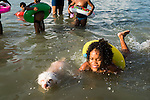"""Bathers enjoy the artificial pool of Piscinão de Ramos, or """"big pool of Ramos"""", in the north zone of Rio de Janeiro, Brazil, on Saturday, November 1, 2014. Thousands of people who live in the surrounding favelas go every summer. The pool, which opened in December 2001, holds 30 million liters of water."""