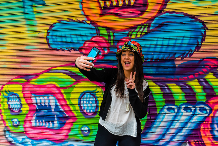 Young woman taking a selfie, Little Italy, New York, New York USA.