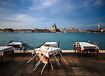 The tables and the chairs of a restaurant on the watefront sidewalk of the Giudecca island in Venice, Italy