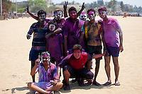 Indian boys celebrating annual Hindu Holi festival of colours with powder paints on beach by Marine Drive, Mumbai, India