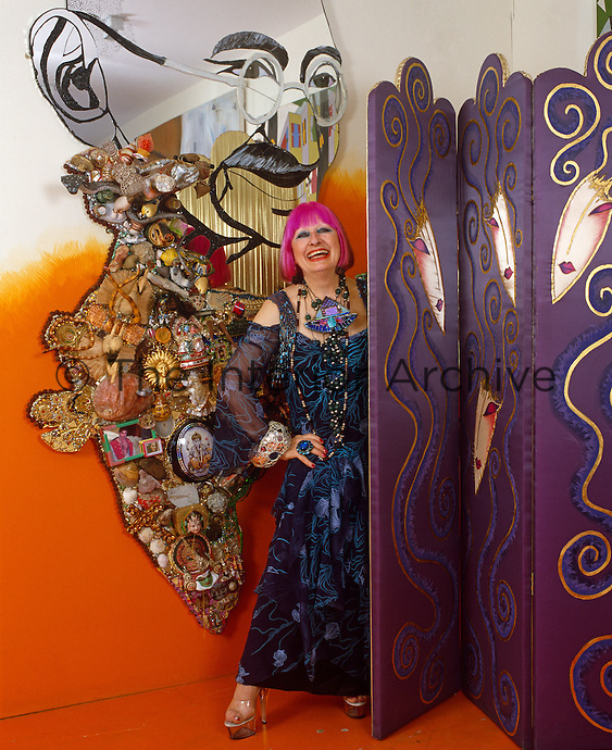 Portrait of Zandra Rhodes appearing from behind a screen laughing