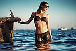 Caucasian female model wearing black swimwear and sunglasses standing outdoors in summer in water