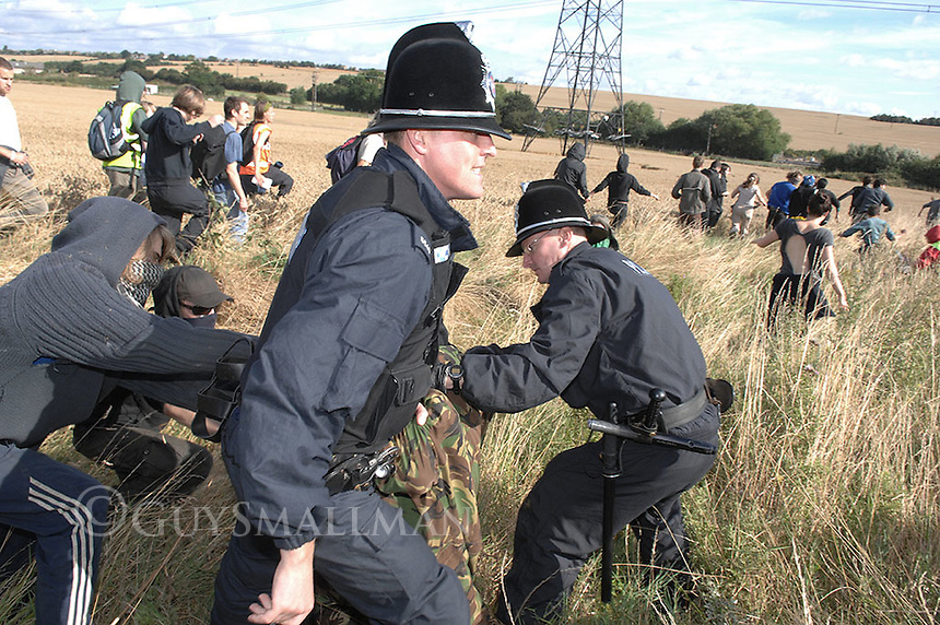 Climate Camp. 9/8/08 Enviromental protesters converge on Kingsnorth in Kent to protest over plans to build a new coal fired power station on the site. Activists head across country to the Power Station. Some scaled the fence others scuffled with the Police. Protesters scuffle with Police near a main road shortly after leaving the camp.