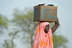A displaced woman walks home after receiving emergency food supplies from the United Nations World Food Program in Agok, a town in the contested Abyei region where tens of thousands of people fled in 2011 after an attack by soldiers and militias from the northern Republic of Sudan on most parts of Abyei. Although the 2005 Comprehensive Peace Agreement called for residents of Abyei--which sits on the border between Sudan and South Sudan--to hold a referendum on whether they wanted to align with the north or the newly independent South Sudan, the government in Khartoum and northern-backed Misseriya nomads, excluded from voting as they only live part of the year in Abyei, blocked the vote and attacked the majority Dinka Ngok population. The African Union has proposed a new peace plan, including a referendum to be held in October 2013, but it has been rejected by the Misseriya and Khartoum. The Catholic parish of Abyei, with support from Caritas South Sudan and other international church partners, has maintained its pastoral presence among the displaced and assisted them with food, shelter, and other relief supplies.