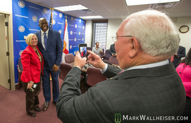 """Florida Senator Bill Montford, right, takes a photo of his assistant Marsha Mathis with  Earvin """"Magic"""" Johnson, retired professional basketball player and current president of operations for the Los Angeles Lakers of the NBA, before a meeting with the Florida Senate Democratic Caucus  about health care at the Florida Capitol in Tallahassee Florida March 13, 2017."""