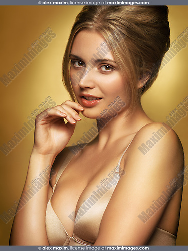 Sensual beauty portrait of young glamorous woman wearing a bra in golden colors on gold background