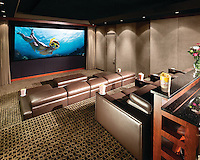 A beautiful theater with ample seating and a functional rear bar area for entertaining guests.  Hidden B&W speakers do not detract from the elegant acoustic panels that help the room sound as elegant as it looks.