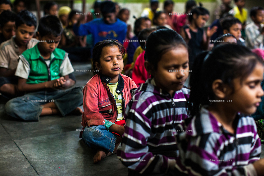 Children of women in prostitution fall asleep during a calming meditation session that Santwana Manju of Guria conducts every evening in the Guria Non-Formal Education center in the middle of the Shivdaspur red light district, Varanasi, Uttar Pradesh, India on 20 November 2013. Santwana Manju developed this form of therapeutic meditation to help the children reduce daily stress and promote a calm mind and emotions.