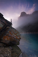 Tower of Babel at Moraine lake with Lichen covered rock and rising mist fanning from the top of the tower