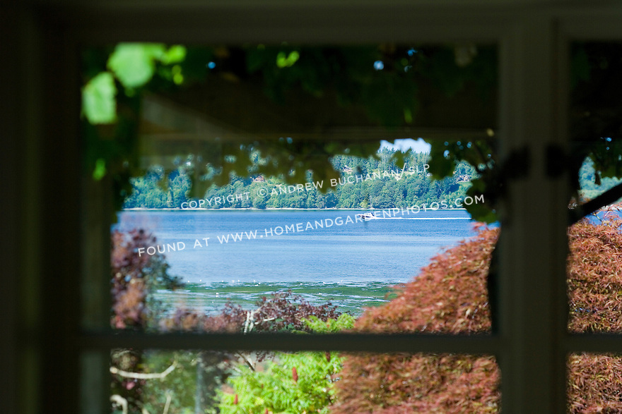 Close-up detail of the view of a boat on the deep blue salt water through a white-painted window frame in soft foreground focus in this waterfront weekend vacation retreat on Washington State's Vashon Island.