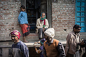 Local villagers take a break outside a grocery store while working on a NREGA project in Medawar Kalan in Ballia district of Uttar Pradesh, India. Photo: Sanjit Das/Panos