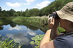Woman birdwatching, Barnes, London, UK, looking through binoculars at birds on water