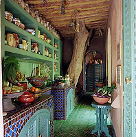The counter and floor tiles in the rustic kitchen were locally crafted and the kitchen units are fitted with Musharabi screens