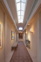 Long hallway features large skylight and art on the walls