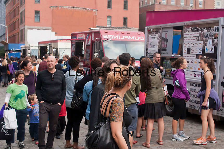 Food trucks in the Brooklyn neighborhood of Dumbo during the 16th Annual Art Under the Bridge Festival on Sunday, September 30, 2012.  Dumbo has been a neighborhood shared by industry and artists but high real estate prices have created opportunities for development with the subsequent increase in condo and co-op development.  (© Richard B. Levine)