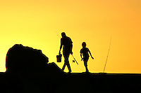 A man and his son finished fishing for the day on the Cottesloe Beach groyne, the setting sun is hidden behind a rock causing the silhouette and yellow sky.