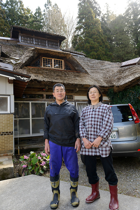 Mountain vegetable farmers Yoshiya and Chie Sato outside their home. Tsuruoka, Yamagata Prefecture, Japan, April 9, 2016. The city of Tsuruoka in Yamagata Prefecture is famous for its sansai mountain vegetable cuisine. These foraged grasses, fungi and vegetables are also used by the mountain ascetics of the Shugendo religion.