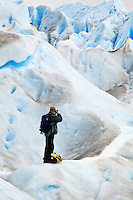 A photographer photographing the vivid blue ice of Glacier Perito Moreno in Parque Nacional los Glaciares, Argentina.