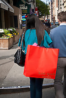 A woman in Noho in New York with a shopping bag filled with her Kate Spade purchases, seen on Saturday, April 28, 2012. Liz Claiborne Inc, parent company of Kate Spade, saw a deceased first quarter loss primarily because of strong Kate Spade and Lucky Brands sales. Liz Claiborne Inc. will be changing tis name to Fifth & Pacific Cos. because of the sale of the Liz Claiborne brand itself. (© Richard B. Levine)