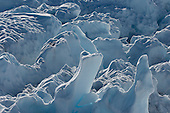 Sunlight and melted water pair up to create unique carved knobs, peaks, and valleys on the Greenland ice sheet.