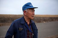 An elderly man observes the damage done to the local area. On 11 March 2011 a magnitude 9 earthquake struck 130 km off the coast of Northern Japan causing a massive Tsunami that swept across the coast of Northern Honshu. The earthquake and tsunami caused extensive damage and loss of life.