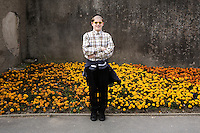 An Hasidic boy poses in front of a municipal flower bed in Aberystwyth.