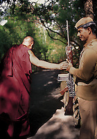 I first met His Holiness the Dalai Lama in 1988 and have had the great fortune to photograph him a number of times over the years. One day we were walking through the lovely bamboo shaded lane from his home to his office as we passed one of his ever-present guards. Suddenly the Dalai Lama stopped. Placing one hand on the soldier's hand holding the rifle, he chanted a prayer and moved on. I quickly lifted my camera and managed to take one frame. The guard simply beamed.