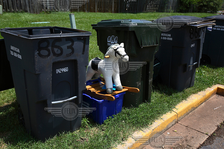 A rocking horse sits between the bins outside a foreclosed house in Manassas, Virginia. The area is suffering from a major collapse in the housing market following the subprime crisis and global credit crunch, which has forced the foreclosure and abandonment of numerous properties...