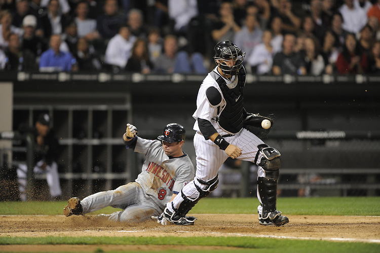 CHICAGO - SEPTEMBER 21:  A.J. Pierzynski #12 of the Chicago White Sox can't catch the ball as Nick Punto #8 of the Minnesota Twins scores in the sixth inning on September 21, 2009 at U.S. Cellular Field in Chicago, Illinois.  The Twins defeated the White Sox 7-0.  (Photo by Ron Vesely)