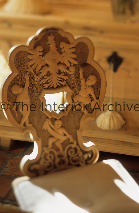 A detail of the back of a wooden chair with carved figures and aeagle inspired emblem