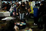 Tourist poses for camera at the tuna auction at the Tokyo Metropolitan Central Wholesale Market or Tsukiji Fish Market is the largest fish market in the world. On December 15 2008, market authorities closed the auction to visitors for a month, citing safety and  health reasons. Authorities said that tourists were getting in the way of workers and touching the fish. Guards are to be placed at entrances to keep visitors away.