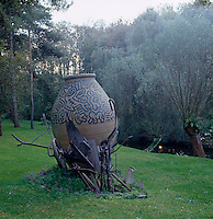 A vase painted by Keith Haring is displayed inside a steel sculpture by Jean Tynguelis in the garden
