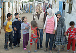 Ahlam Al Khaled, a health and nutrition educator for International Orthodox Christian Charities, walks with children in a settlement of Syrian refugees in Minyara, a village in the Akkar district of northern Lebanon. Lebanon hosts some 1.5 million refugees from Syria, yet allows no large camps to be established. So refugees have moved into poor neighborhoods or established small informal settlements in border areas. International Orthodox Christian Charities, a member of the ACT Alliance, provides support for families in this settlement.