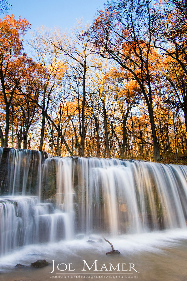 Autumn color in trees line the shore at  Hidden Falls on Prairie Creek in Nerstrand Big Woods State Park, Minnesota.
