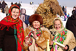 Three women in Ukrainian traditional clothes and a straw man behind them that is going to be burnt on Shrovetide as a symbol of the end of winter Ukraine Eastern Europe 2007