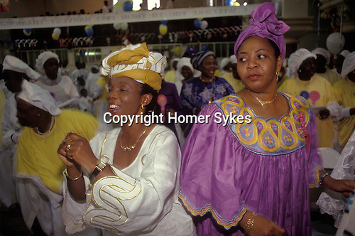 Celestial Church of Christ South London. A daance of Thanksgiving at a Harvest festival Sundayu church service. Yoruba people from western Nigeria mainly make up this churches congreation.  from A STORM IS PASSING OVER a Look at Black Churches in Britain. Published by Thames and Hudson isbn 0 500 27826 1