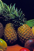 """A Hawaiian """"""""still life"""""""" with two large pineapples surrounded by other island fruits."""