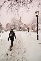 A student walk towards the Ira Allen Statue and Old Mill, UVM Campus Green, Winter UVM Campus