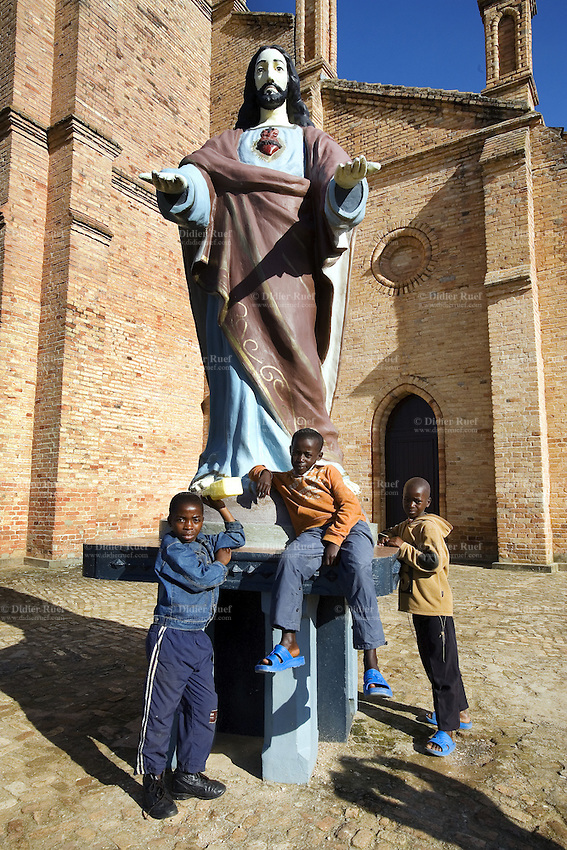 Rwanda. Southern province. Kabgay. District of Muhanga.  Catholic church. A group of three young black boys stand near the statue of Jesus Christ, both his arms open. © 2007 Didier Ruef